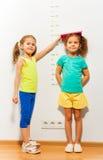 Amico di aiuto della bambina per misurare altezza sulla scala immagine stock libera da diritti