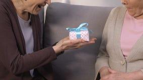 Amico femminile che presenta il contenitore di regalo a signora senior alla casa di cura, festa di compleanno stock footage
