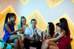 Amico maschio schioccando una bottiglia del champagne mentre amici che lo guardano fotografia stock