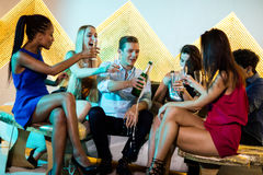 Amico maschio schioccando una bottiglia del champagne mentre amici che lo guardano fotografie stock