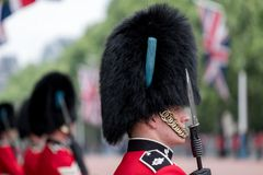 Amid tight security, Royal Guards in red and black uniform and bearskins line The Mall in London for Trooping the Colour Parade Stock Photo