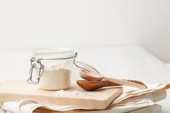 Amidon, soude dans le pot et deux cuillères en bois Photos stock