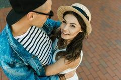 Amie élégante dans le chapeau en paille de paille et son ami étreignant sur la rue Images stock