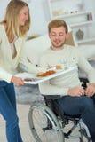 Amie affectueuse salut l'ami dans le fauteuil roulant Photo libre de droits