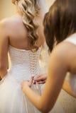 Amie attachant la jeune mariée de corset sur le mariage Photo stock