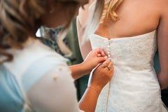 Amie attachant le blanc de robe de mariage de corset de jeune mariée Photographie stock libre de droits