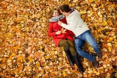 Amie avec l'ami se trouvant sur les feuilles tombées en parc Photo libre de droits