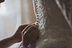 Amie boutonnant la robe de mariage pour la jeune mariée 558 Photo stock
