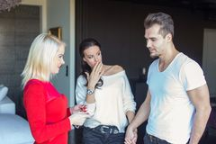 Amie choquée sur l'ami déloyal flirtant avec l'OE blond Image stock