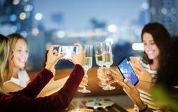 Amie dînant ensemble à une barre de dessus de toit prenant a photographie stock