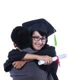 Amie d'étreinte d'ami sur l'obtention du diplôme - d'isolement Image libre de droits