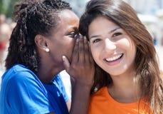 Amie d'afro-américain et de Caucasien chuchotant dans la ville Photo stock