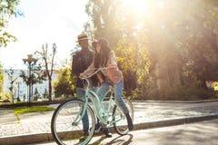 Amie de aide d'ami montant un vélo Image libre de droits