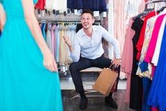 Amie de aide d'homme pour choisir la robe Photo stock