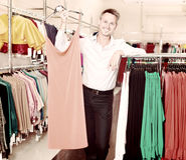 Amie de aide d'homme pour choisir la robe Images libres de droits