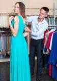 Amie de aide d'homme pour choisir la robe Photo libre de droits