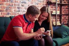 Amie de aide de garçon avec le smartphone quand ils reposent le pouvoir adiathermique Image stock