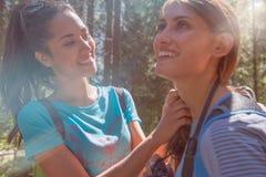 Amie de aide de sourire de femme au chemin de sentier de randonnée en bois de forêt pendant le jour ensoleillé Groupe d'été de pe Image stock