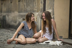Amie de deux filles avec un chat se reposant sur le trottoir sur la rue Images stock