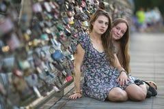 Amie de deux jeunes filles s'asseyant sur le pont de l'amour avec des serrures Photographie stock libre de droits