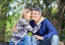 Amie de embrassement d'homme au terrain de camping Photographie stock