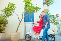 Amie de embrassement de jeune homme s'asseyant sur le scooter garé sur la rue méditerranéenne de ville avec les pots exotiques de Photographie stock libre de droits