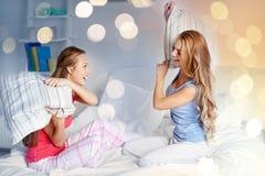 Amie de l'adolescence heureux combattant des oreillers à la maison Image stock
