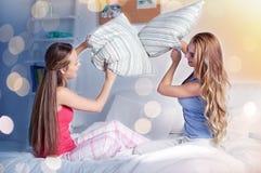 Amie de l'adolescence heureux combattant des oreillers à la maison Photo libre de droits