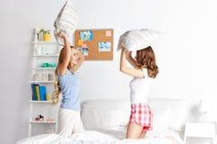 Amie de l'adolescence heureux combattant des oreillers à la maison Photos stock