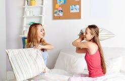 Amie de l'adolescence heureux combattant des oreillers à la maison Image libre de droits