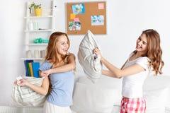 Amie de l'adolescence heureux combattant des oreillers à la maison Photo stock