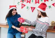 Amie de l'Asie utilisent le chapeau de Santa à la joyeuse fête de Noël et ex Photographie stock