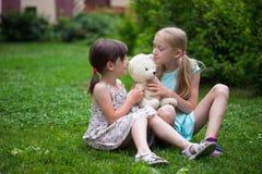 Amie de petite fille sur la pelouse Image libre de droits