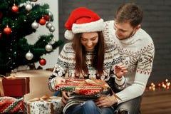 Amie de sourire heureuse de brune dans le chapeau rouge de Santa déroulant le ch Photos libres de droits