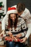 Amie de sourire heureuse de brune dans le chapeau rouge de Santa déroulant le ch Photographie stock