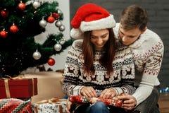 Amie de sourire heureuse de brune dans le chapeau rouge de Santa déroulant le ch Photos stock