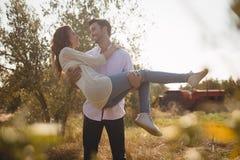 Amie de transport de sourire de jeune homme à la ferme olive Photographie stock libre de droits