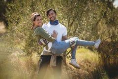 Amie de transport de sourire de jeune homme par des arbres à la ferme Photo stock