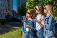 Amie de trois filles Été en nature Dans des ses mains tient un smartphone Fait des photos au téléphone Le concept de l'école Photographie stock libre de droits