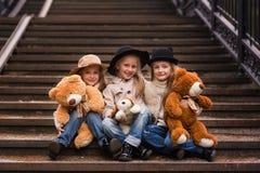 Amie drôle de fille s'asseyant sur les escaliers avec les jouets mous en parc Photo stock