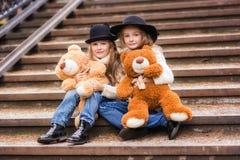 Amie drôle de fille s'asseyant sur les escaliers avec les jouets mous en parc Photo libre de droits