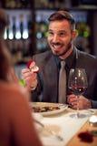 Amie engagée par homme dans le restaurant Photos stock