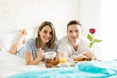 Amie et ami de sourire prenant le petit déjeuner sain dans le lit photo libre de droits