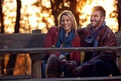 Amie et ami de sourire sur le banc en parc Photo stock