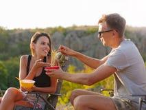 Amie et ami mangeant des nouilles sur un fond naturel Couples de touristes heureux ayant l'amusement Concept bon marché de touris Images stock
