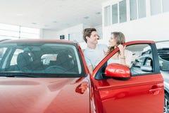 Amie et ami regardant l'un l'autre et se tenant près de la voiture rouge Images stock
