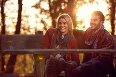 Amie et ami sur le banc en parc Images libres de droits