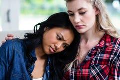 Amie féminine déprimée de consolation de jeune femme à la maison Images stock