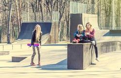 Amie faisant de la planche à roulettes au parc Image libre de droits