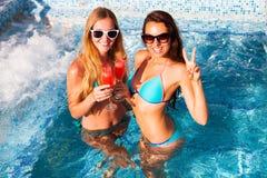 Amie heureuse avec une boisson sur une partie d'été par la piscine Image stock